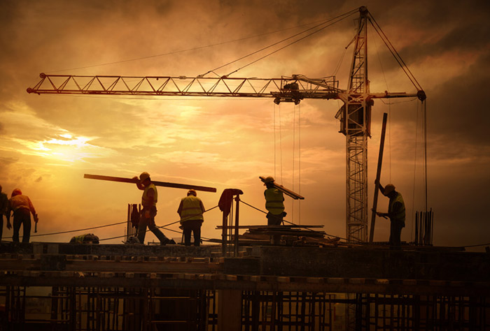 workers on construction platform at sunset